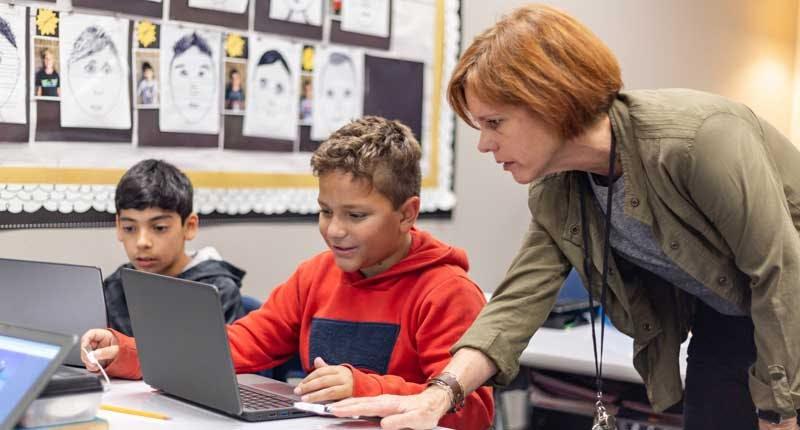 A teacher helping a student playing ST Math.